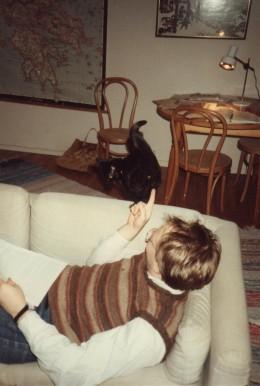 """Vår katt Pollux uppvaktar mig när jag pluggar. I bakgrunden: """"Jägarna i snön"""" samt en karta över det antika Grekland."""